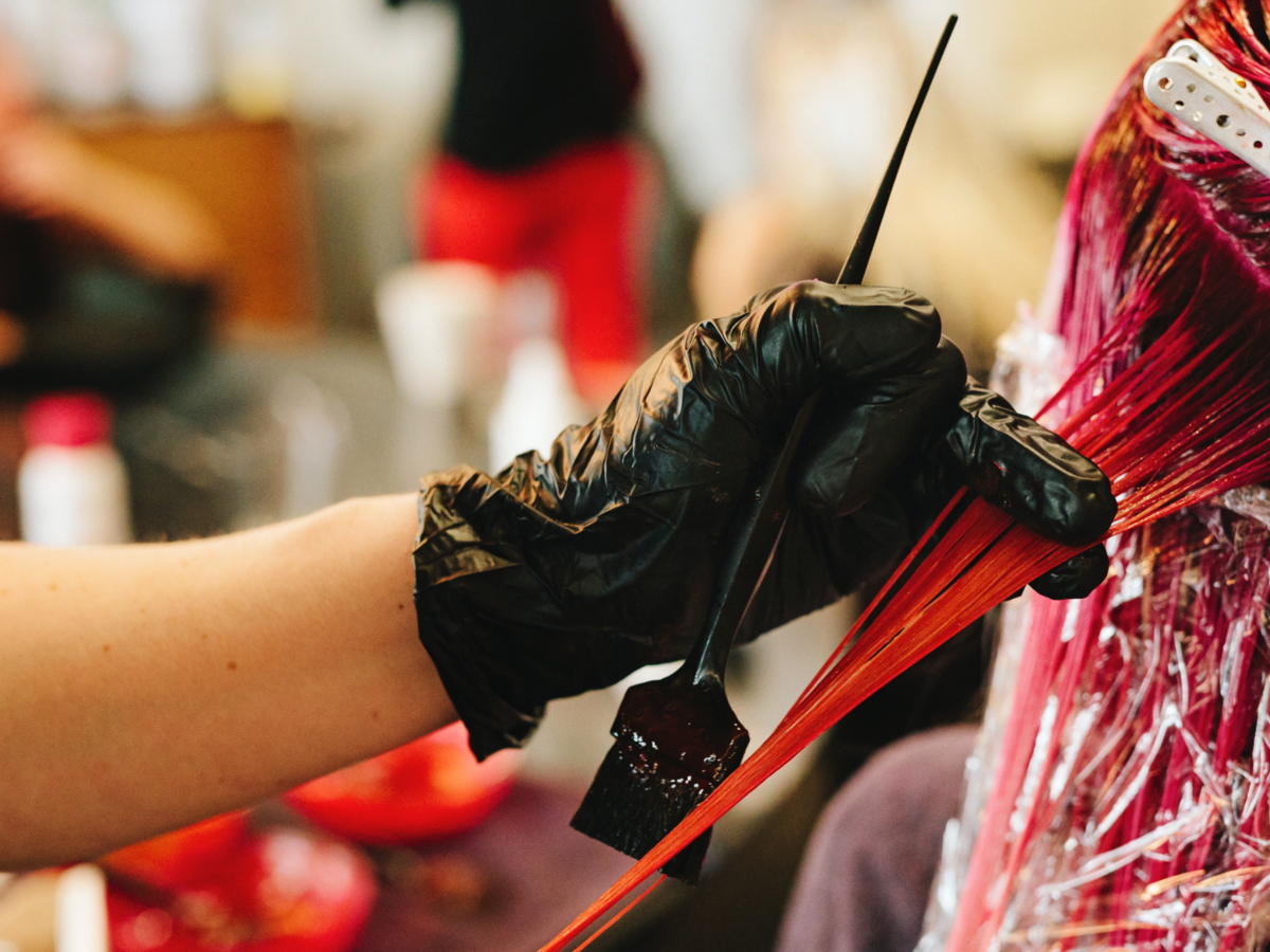 Black gloved hands putting pink dye in hair