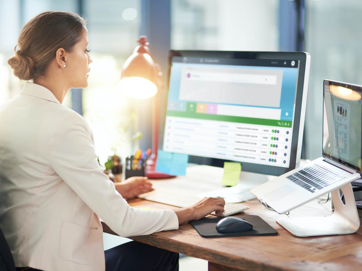 Woman sitting at desk in front of a computer monitor and laptop computer