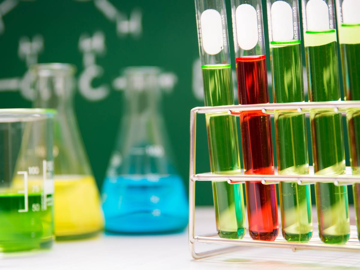 Beaker, flasks and test tubes in a stand with green and red liquid
