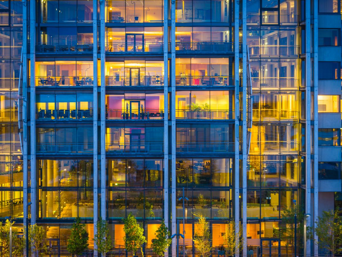 Business office building windows illuminated at dusk