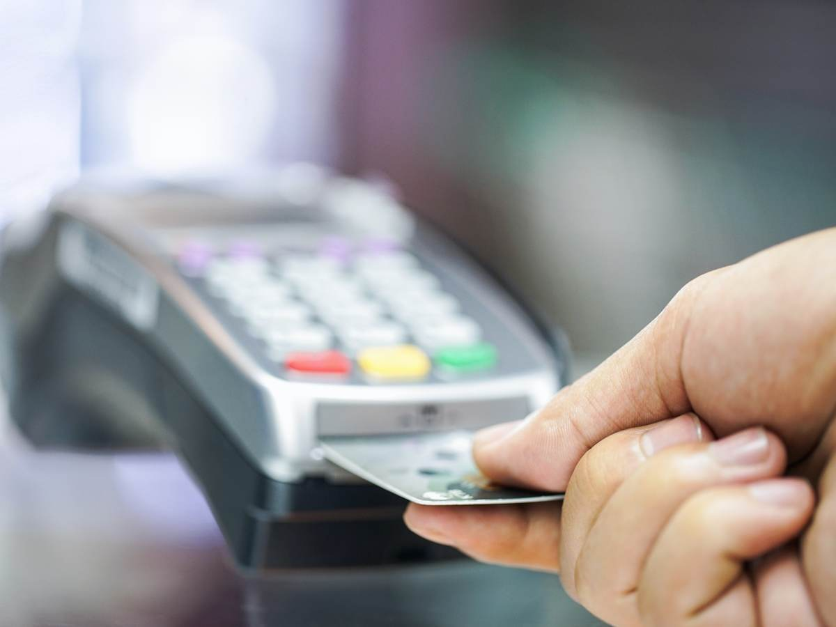 man inserting a credit card into a payment terminal