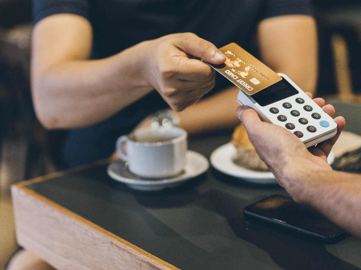 man paying with a credit card in cafe