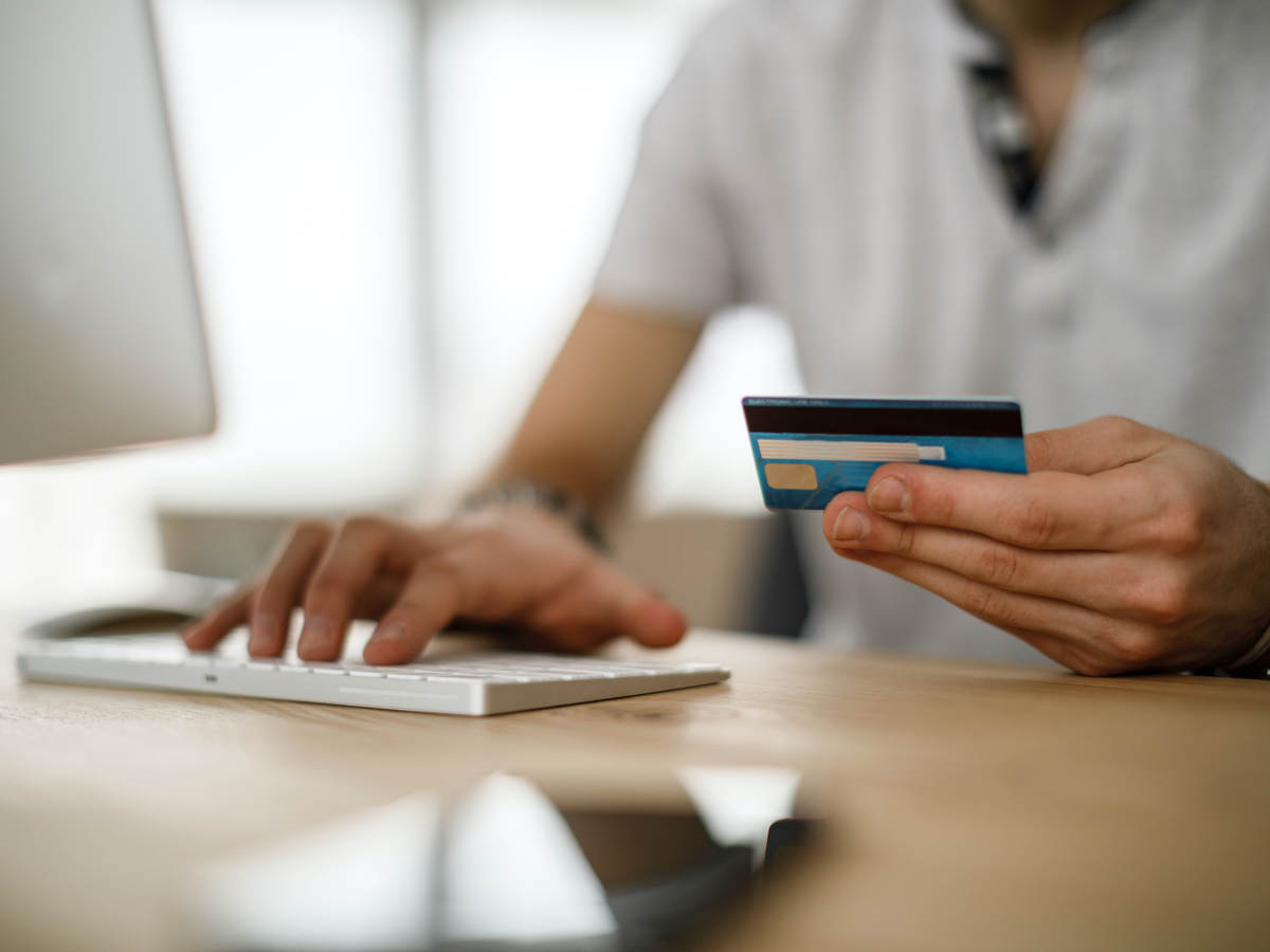 man typing on keyboard and holding a credit card for online payment