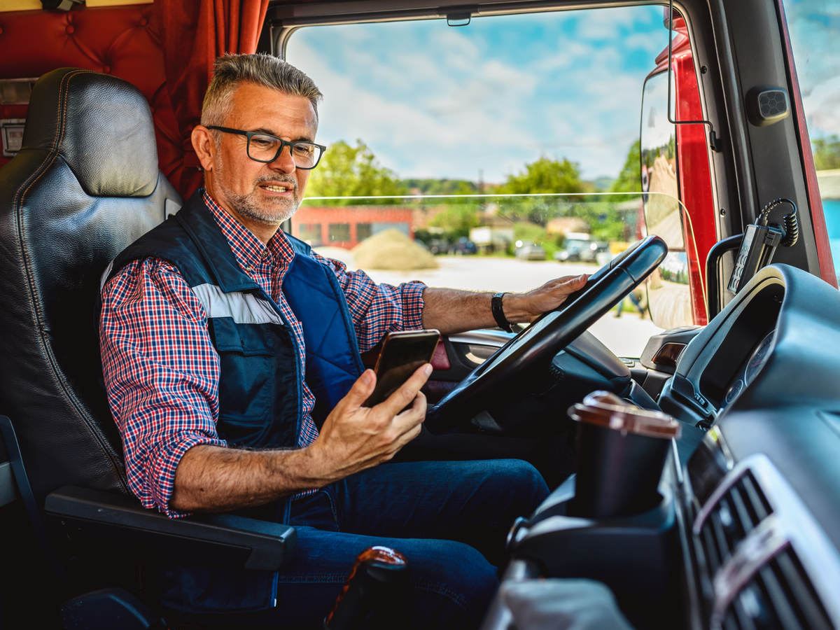 man looking at a mobile phone in the truck