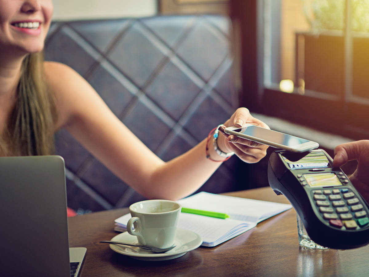 woman tapping a mobile phone for payment in cafe