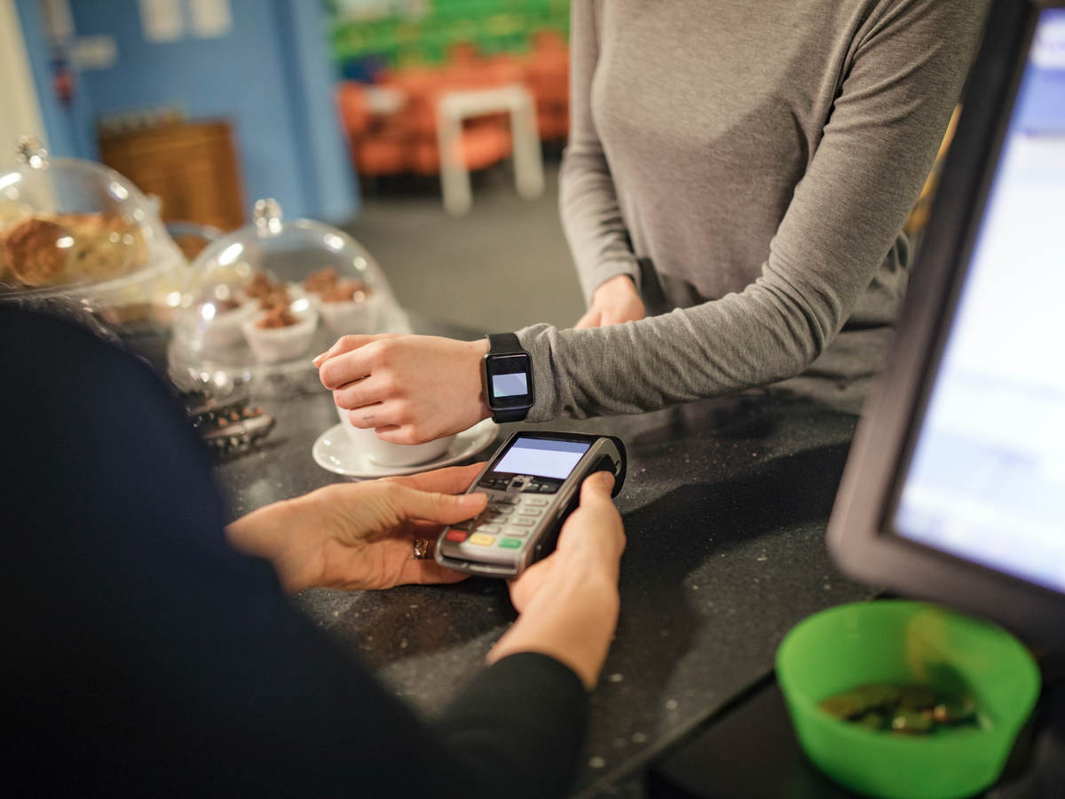 woman using a smartwatch for payment in cafe