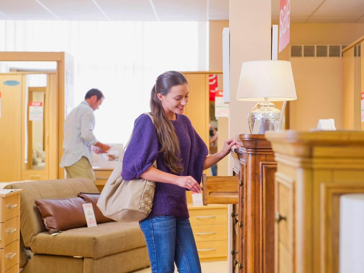 People looking for furnishings in furniture retailer store.