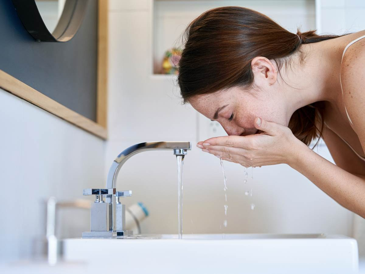 Person washing their face over a sink