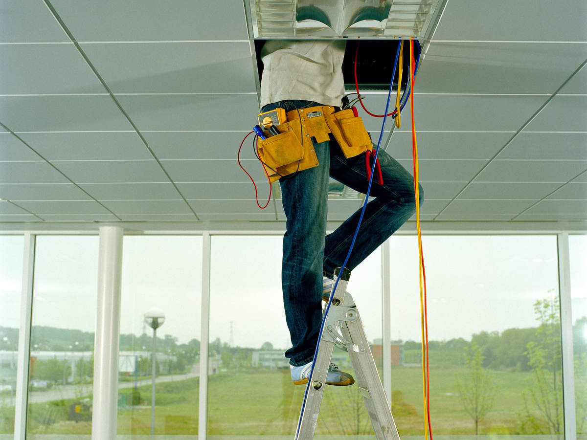 Man on step ladder, working through gap in ceiling, low section