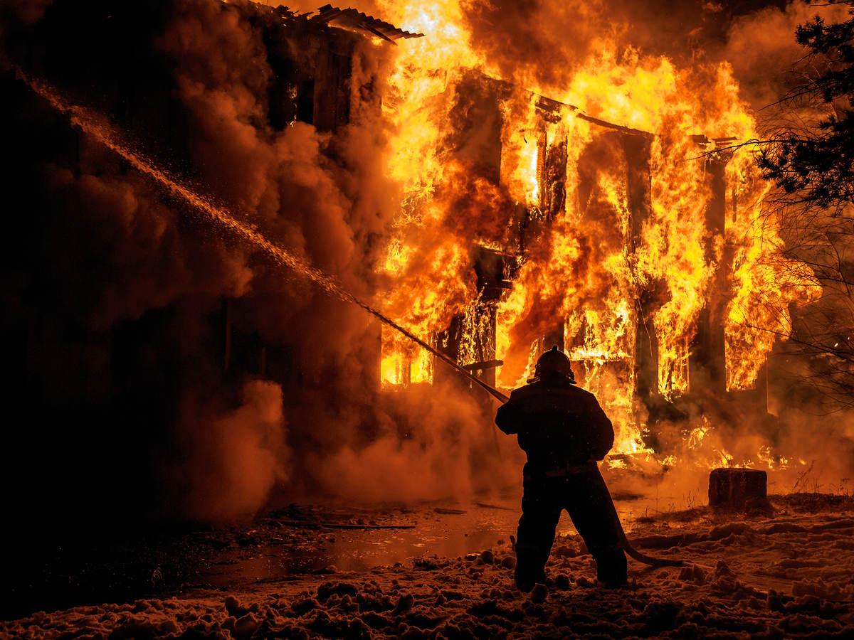 Man in fire gear fighting building fire