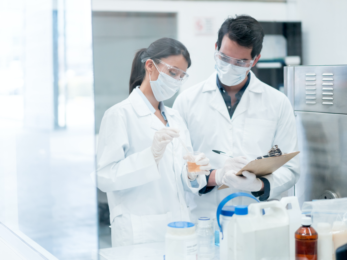 Two brunette scientists in lab with white coats