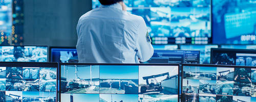 Person standing in a control room looking at security video feeds