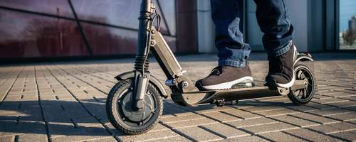 close up view of the legs of a man on an electric scooter.