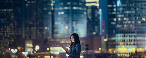 Woman looking at her tablet at night in the city