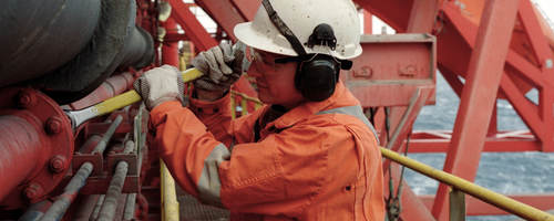 Working in a hard hat working in a petroleum refinery