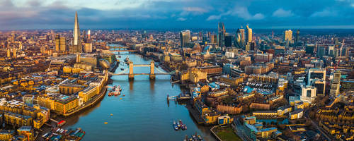 Golden hour aerial view of London's skyline, including the Tower Bridge and famous skyscrapers.
